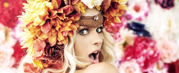 Frau mit Kopfschmuck aus Blumen vor einer Blumenwand schaut über ihre Schulter in die Kamera.