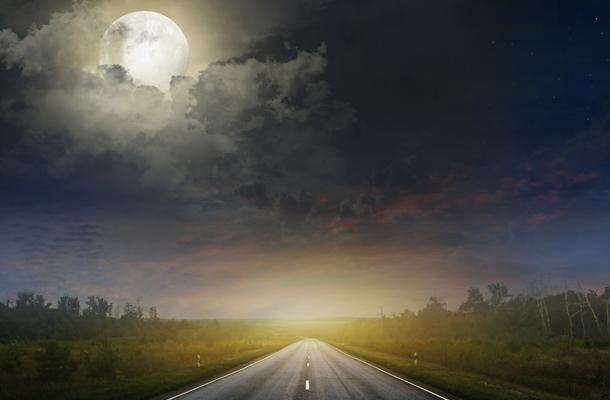 Landstraße bei Sonnenaufgang mit hellem Mond hinter den Wolken