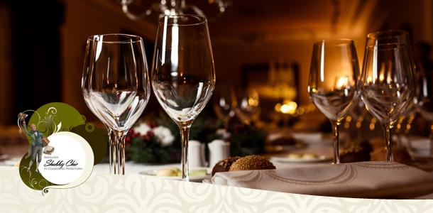 Gedeckter Tisch im Restaurant mit Restaurant Logo im Vordergrund auf einer Borde
