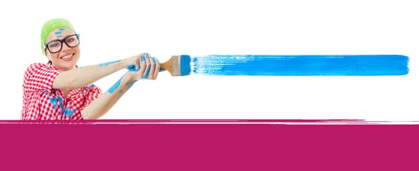 Frau streicht blau hinter rosa Fläche