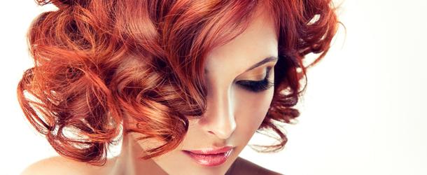 Frau mit lockigen roten Haaren schaut zum Boden-